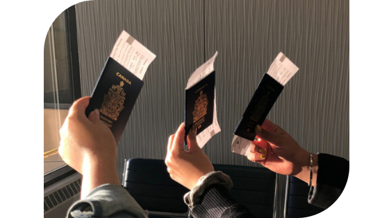 Three hands holding up Canadian passports